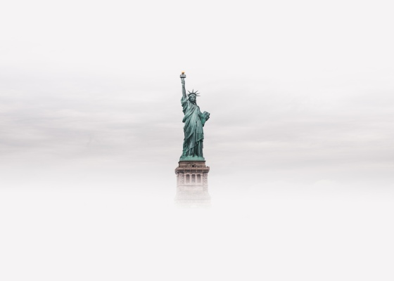 Statue of Liberty rising out of fog. Photo courtesy of Luke Stackpoole via Unsplash