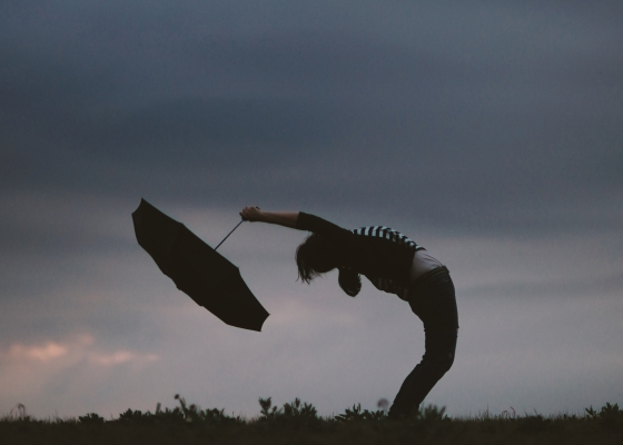 woman holding an umbrella under a stormy sky, bent over backwards so her open face is facing up toward the storm